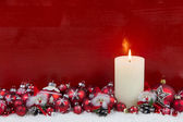 Red wooden christmas background with one burning advent candle. — Zdjęcie stockowe