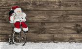 Fondo de madera de navidad con santa en una bicicleta. saludo gracioso — Foto de Stock