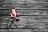 Funny red santa claus on wooden grey background in hurry for buy — Stock Photo
