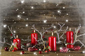 Xmas decoration on wooden rustic background: four red burning ad — Foto Stock