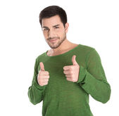 Happy isolated young man in green pullover making thumb up gestu — Stock Photo