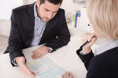 Adviser sitting in a meeting with a blank on the table explainin — Stock Photo