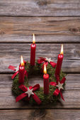 Four red burning advent candles on wooden background for christm — Zdjęcie stockowe