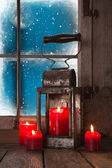 Christmas atmosphere: four red burning candles in the window. — Stock Photo