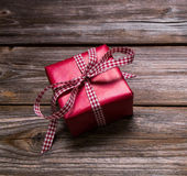 One red christmas present wrapped in red paper with checked ribb — Stock Photo