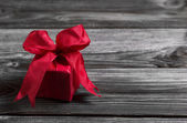 One red festive christmas present on wooden shabby background. — Zdjęcie stockowe