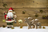 Christmas decoration: Santa Claus with wooden reindeer on backgr — Zdjęcie stockowe
