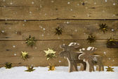 Two wooden handmade reindeer on a background with golden stars a — Stockfoto