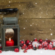 Christmas latern with red candle and balls on wooden background. — Stock Photo #51234431