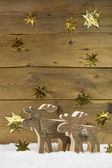 Two wooden elks on wooden christmas background. — Zdjęcie stockowe