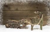 Handmade elk or reindeer with slide of wood on wooden background — Stock fotografie