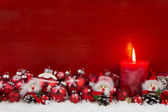 Red christmas candle with balls and imp on wooden background. — Stock Photo