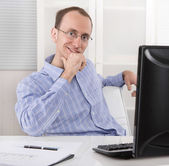 Satisfied businessman sitting in his office with computer. — ストック写真