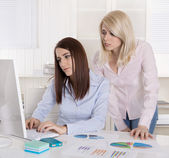 Two young businesswoman looking disappointed at the screen in th — Stock Photo