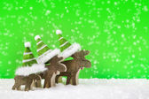 Three wooden reindeer for christmas on a green background with s — Stock Photo
