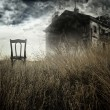 Abandoned chair out in a field facing a haunted house — Stock Photo