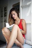 Młoda kobieta w oknie czytanie książki — Zdjęcie stockowe