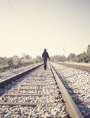 Woman walking on railway tracks — Стоковое фото