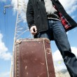 Man with suitcase in a field — Stock Photo
