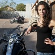 Young female stands by parked motorcycles — Stock Photo