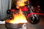 Motorcycles parked between barrels with fire — Stock Photo