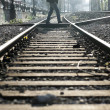 Man crossing railway tracks — Stockfoto