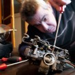 Постер, плакат: Mecanic repairs a carburetor