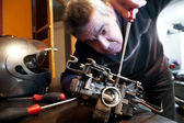 Mecanic repairs a carburetor — Stock Photo