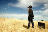 Man with binoculars in a field — Stock Photo