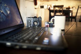 Laptop and film camera on table — Stock Photo
