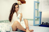 Young female sitting on bed — Stockfoto
