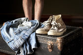 Pair of jeans and sneakers on suitcase — Foto de Stock