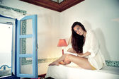 Young female reading book on bed — Foto de Stock