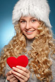 Girl in winter clothes giving heart. — Stock Photo
