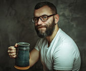 Happy man drinking beer from the mug — Stock Photo
