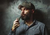 Man smokes a pipe standing near the wall — Stock Photo