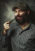 Portrait of young stylish man with a beard with a pipe — Foto de Stock