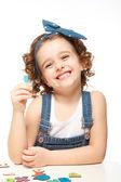 Dziewczynka gra w alfabecie. pokazuje na literę l. — Zdjęcie stockowe