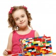 Stockfoto: Small girl builds house from plastic blocks