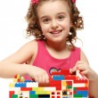 Small girl builds a house from plastic blocks — Stock Photo #40853379