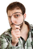 Man in green shirt looking through a magnifying glass. — Stock Photo