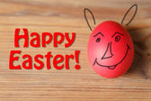 Red easter egg on wooden table — Stock Photo