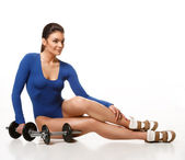 Woman bodybuilder posing after a workout near dumbbells — Stock Photo