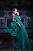 Beautiful woman in a green long dress on a background of richly  — Stok fotoğraf