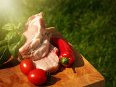 Raw pork steaks on wooden table with tomatoes, peppers and basil — Stock Photo