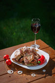 Grilled pork steaks on a wooden table with a glass of wine — Stock Photo