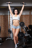 Woman bodybuilder training with dumbbell. — Foto Stock