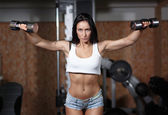 Woman bodybuilder training with dumbbell. — Foto de Stock