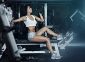 Young beautiful woman is training in the gym — Stok fotoğraf