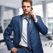 Businessman in office talking on cell phone — Stock Photo #49634271